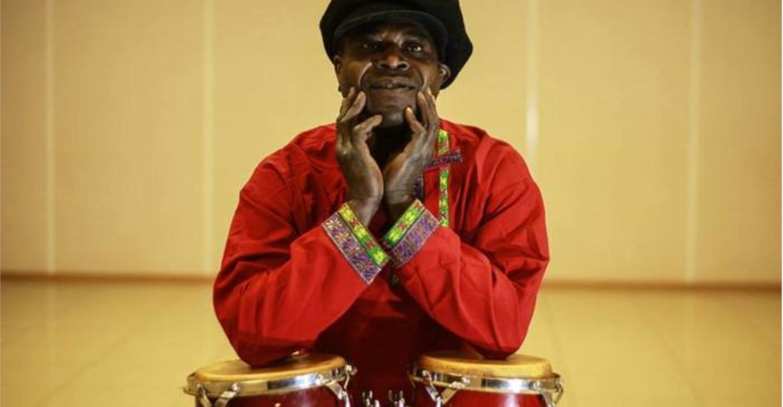 Негр играет drum на барабанах прямо на улице