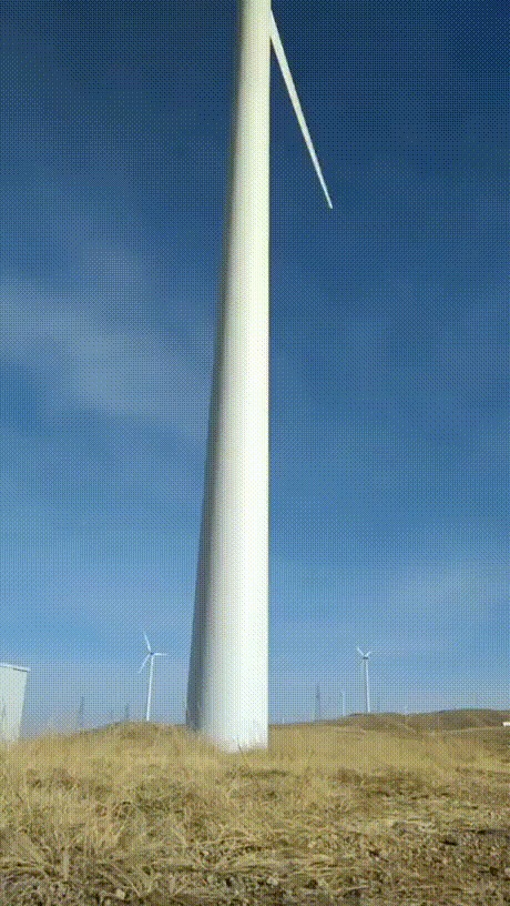 Человек как шкала на фоне ветряной турбины