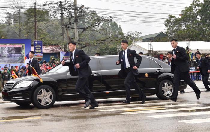 Ким Чен Ын во Вьетнаме едет на бронированном автомобиле, рядом с которым по периметру бегут охранники.