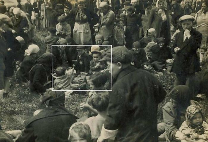 Малыш дарит мальчику постарше цветок после прибытия в Освенцим в мае 1944 года. Все на фотографии будут мертвы в течение нескольких часов.
